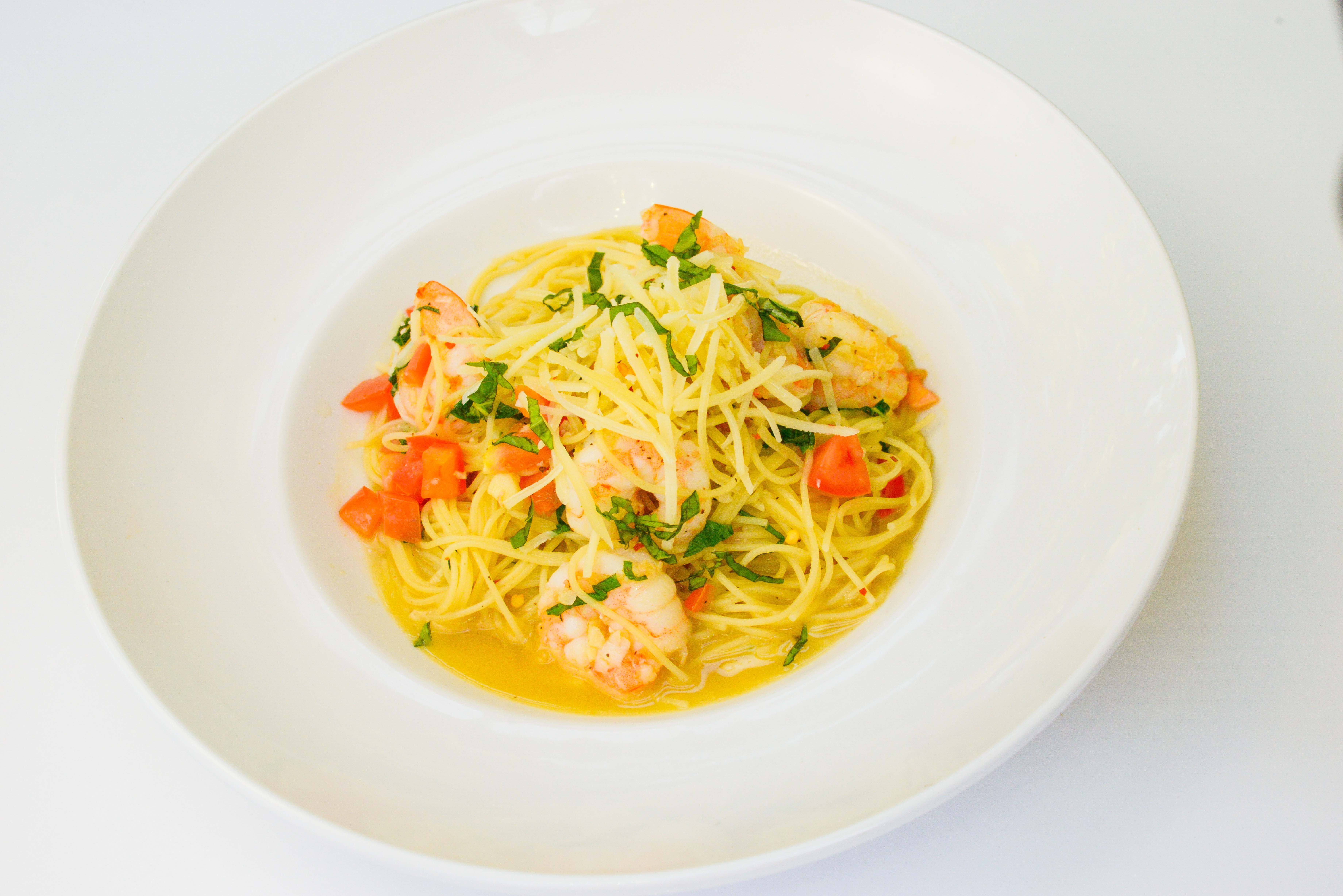 Dish with spaghetti, shrimp, tomatoes, and shredded basil leaves