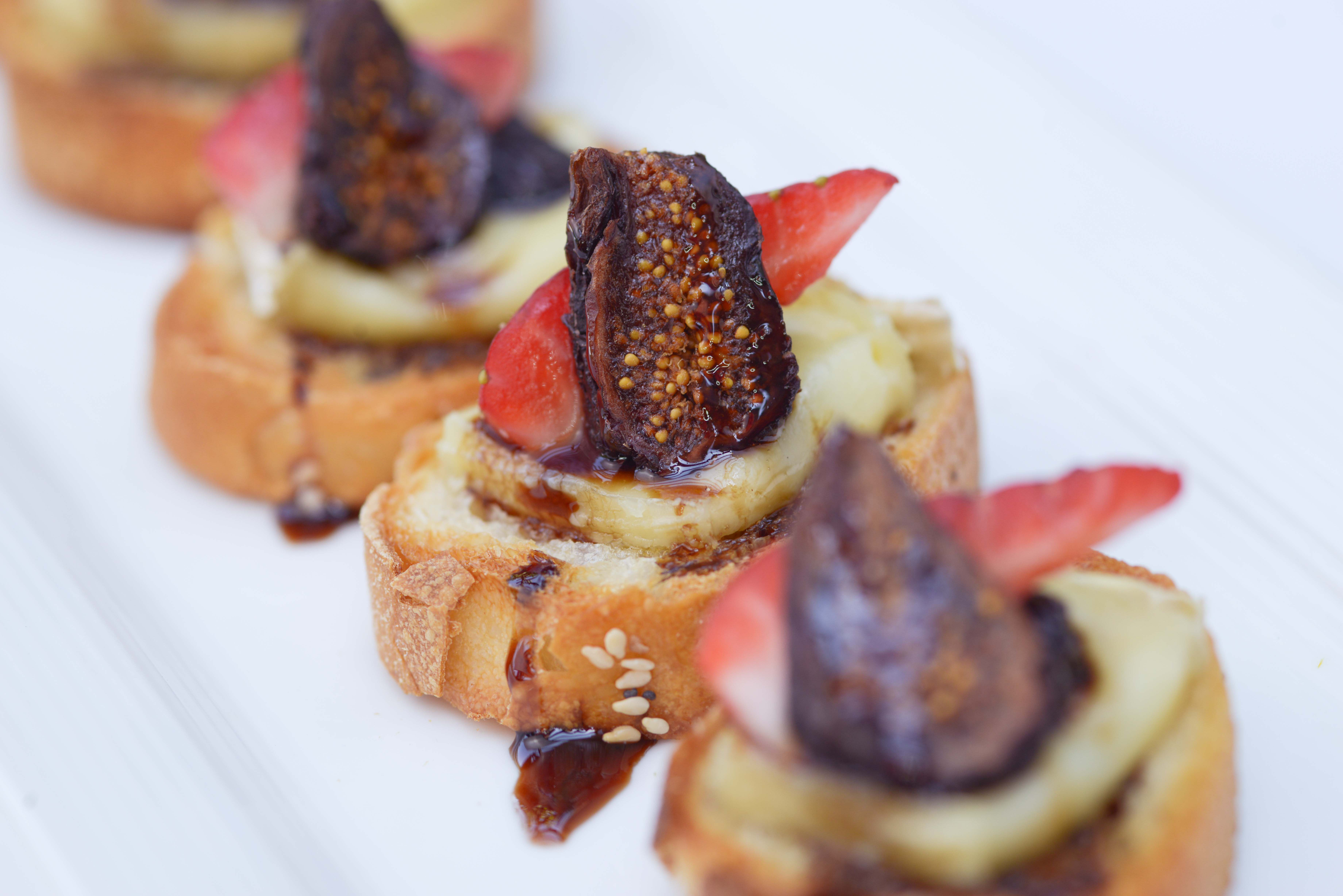 Row of pastry desserts flled with cream and topped with halved strawberries and figs