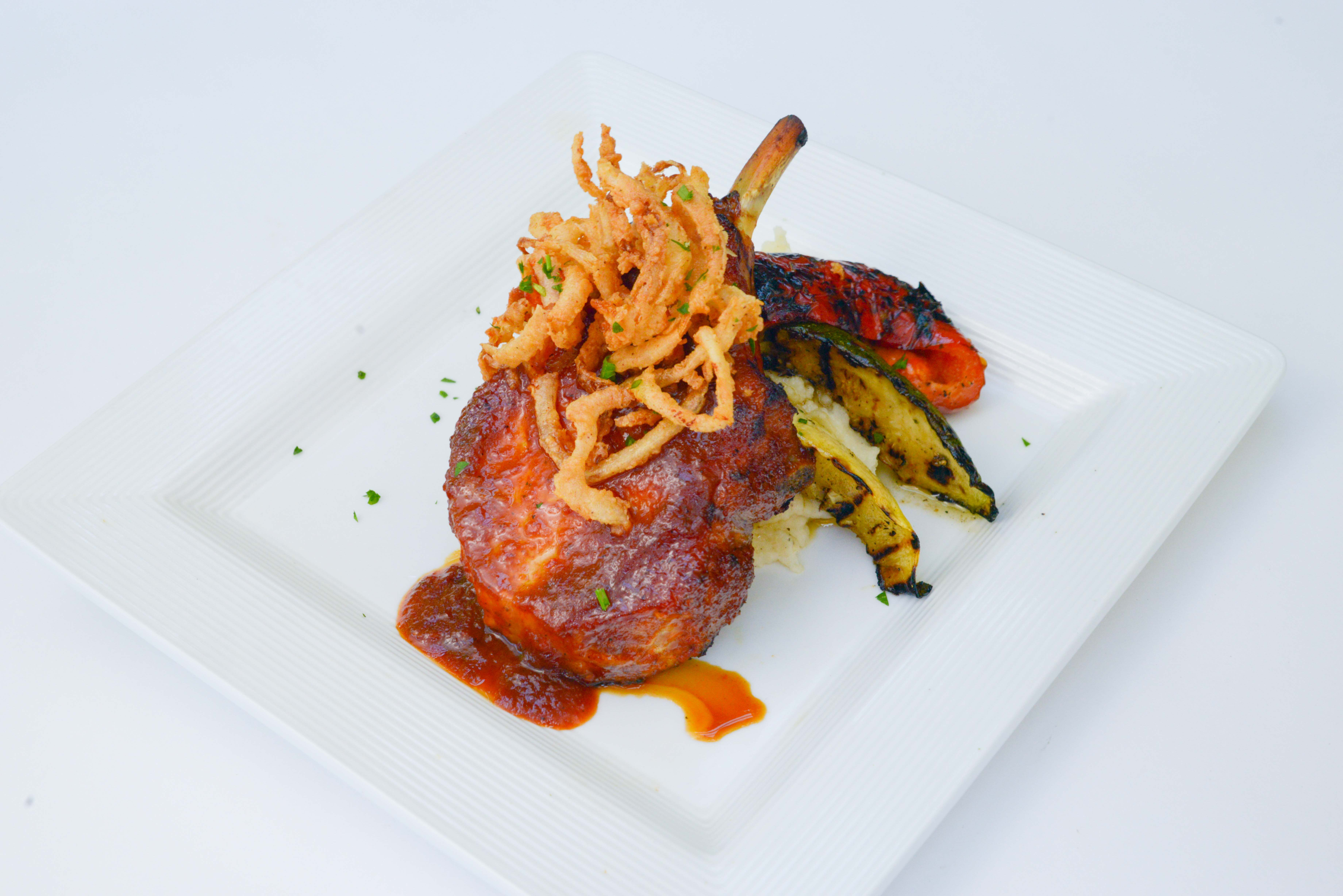 Beef glazed with sauce, topped with crispy onions and served alongside charred vegetables